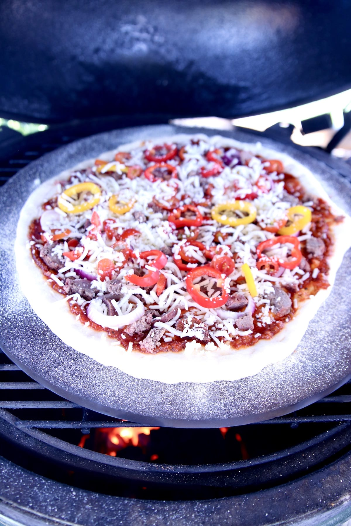 pizza on a grill with pizza stone