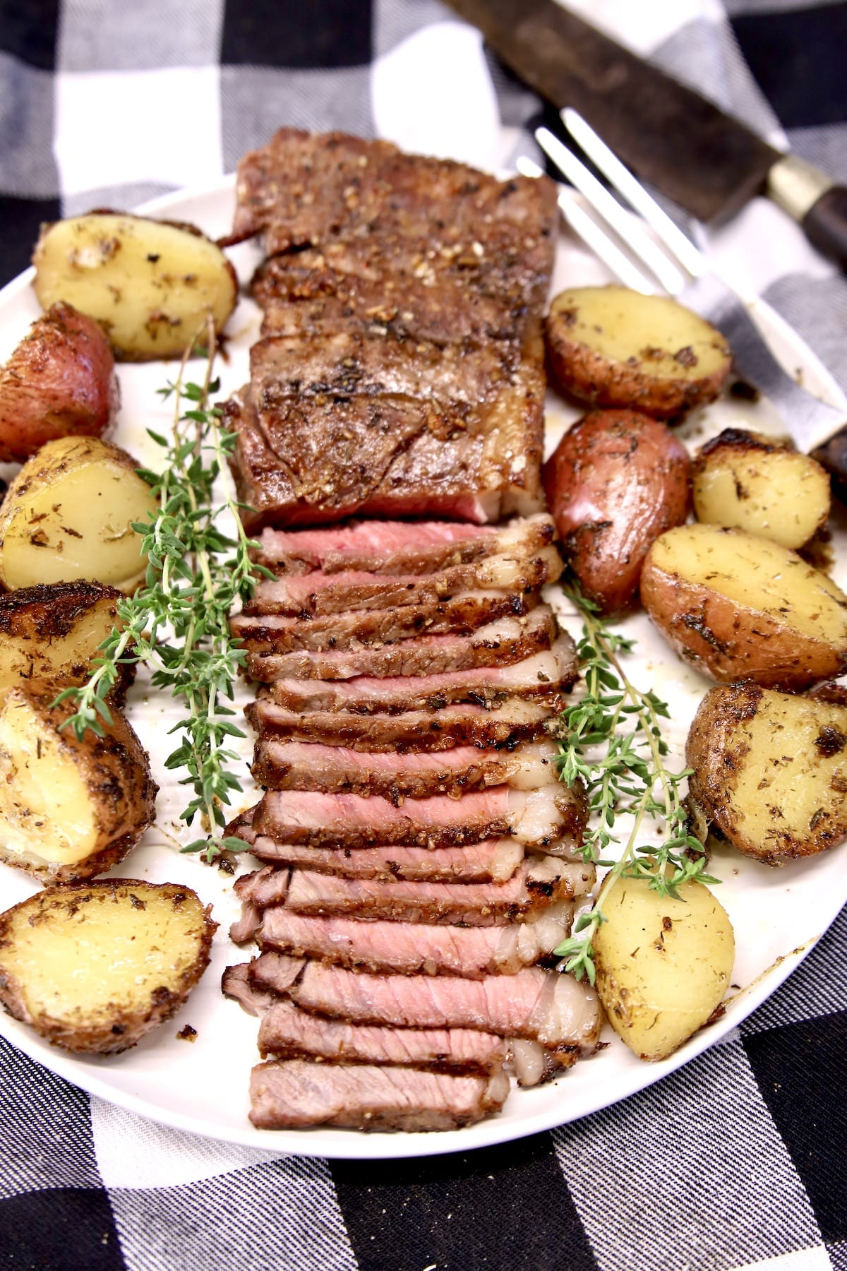 Grilled Strip Steak - partially sliced on a plate with roasted potatoes