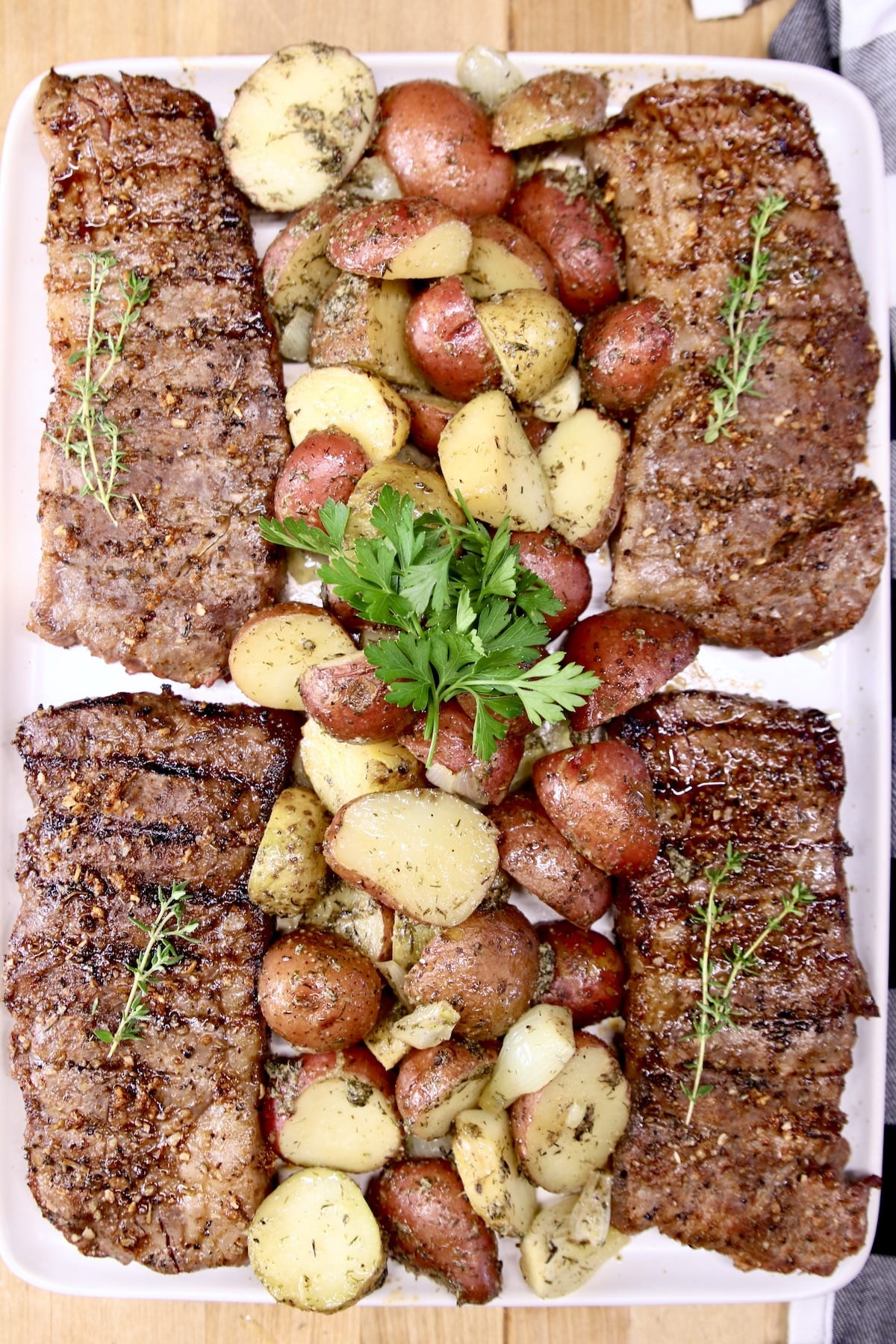 4 NY Strip Steaks on a platter with roasted potatoes in center