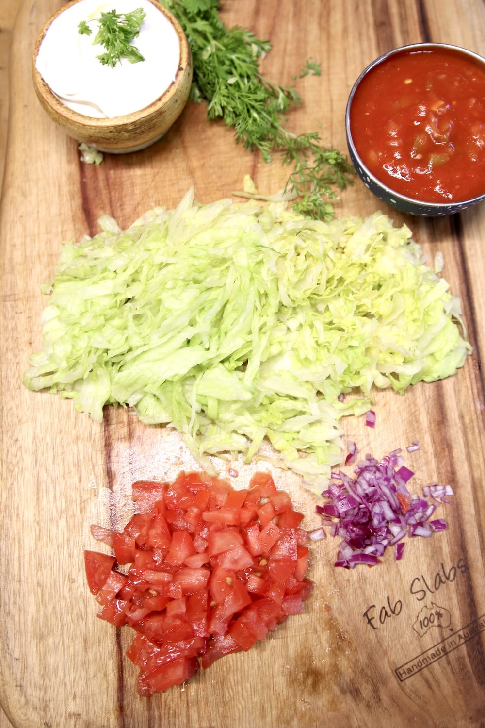 cutting board with sour cream, salsa, lettuce, tomatoes onions for topping enchiladas