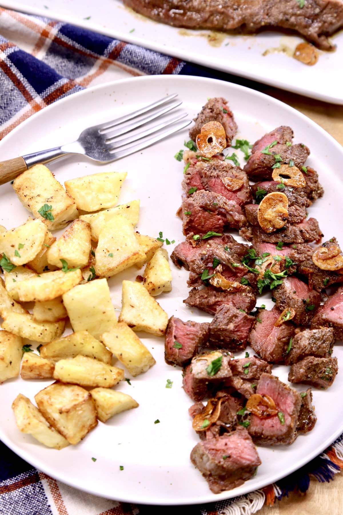garlic butter steak tips cut into bites on a plate with roasted potatoes