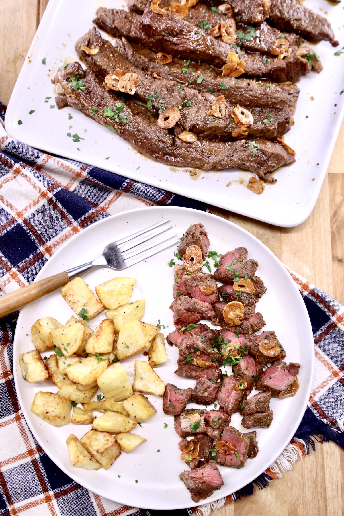 steak tips on a platter and plated, sliced with potatoes