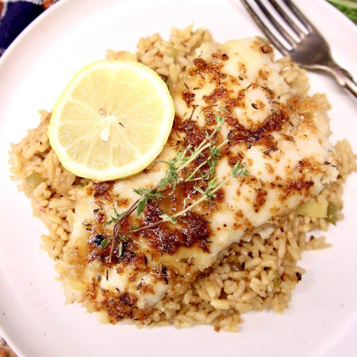 grilled catfish over rice pilaf, lemon garnish