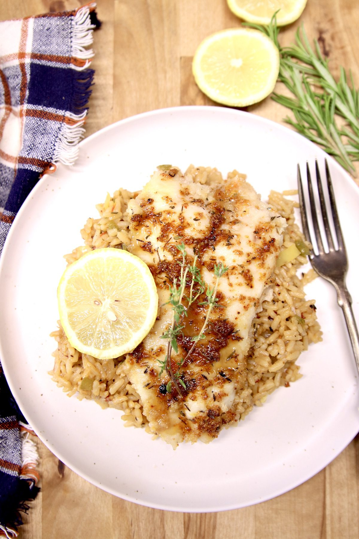 Grilled Catfish Filets over rice with lemon and herb garnish