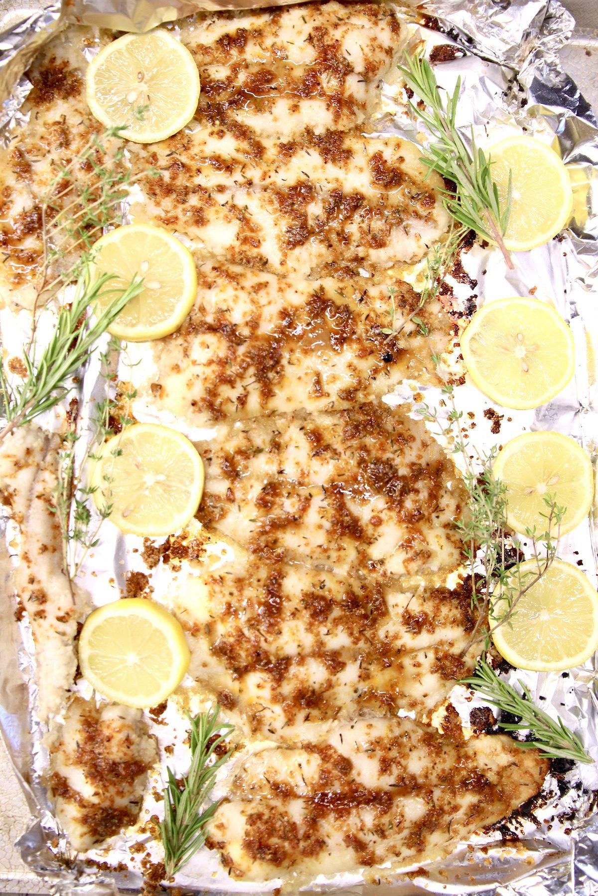 fish filets with lemon rub, lemon and herb garnish