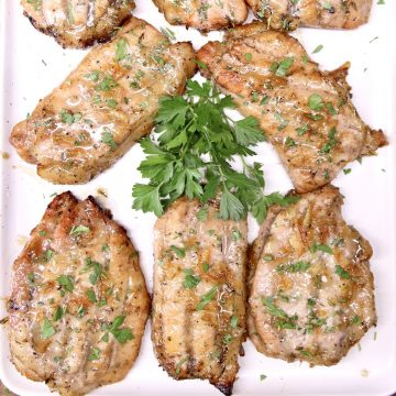 Platter of grilled pork chops with parsley garnish