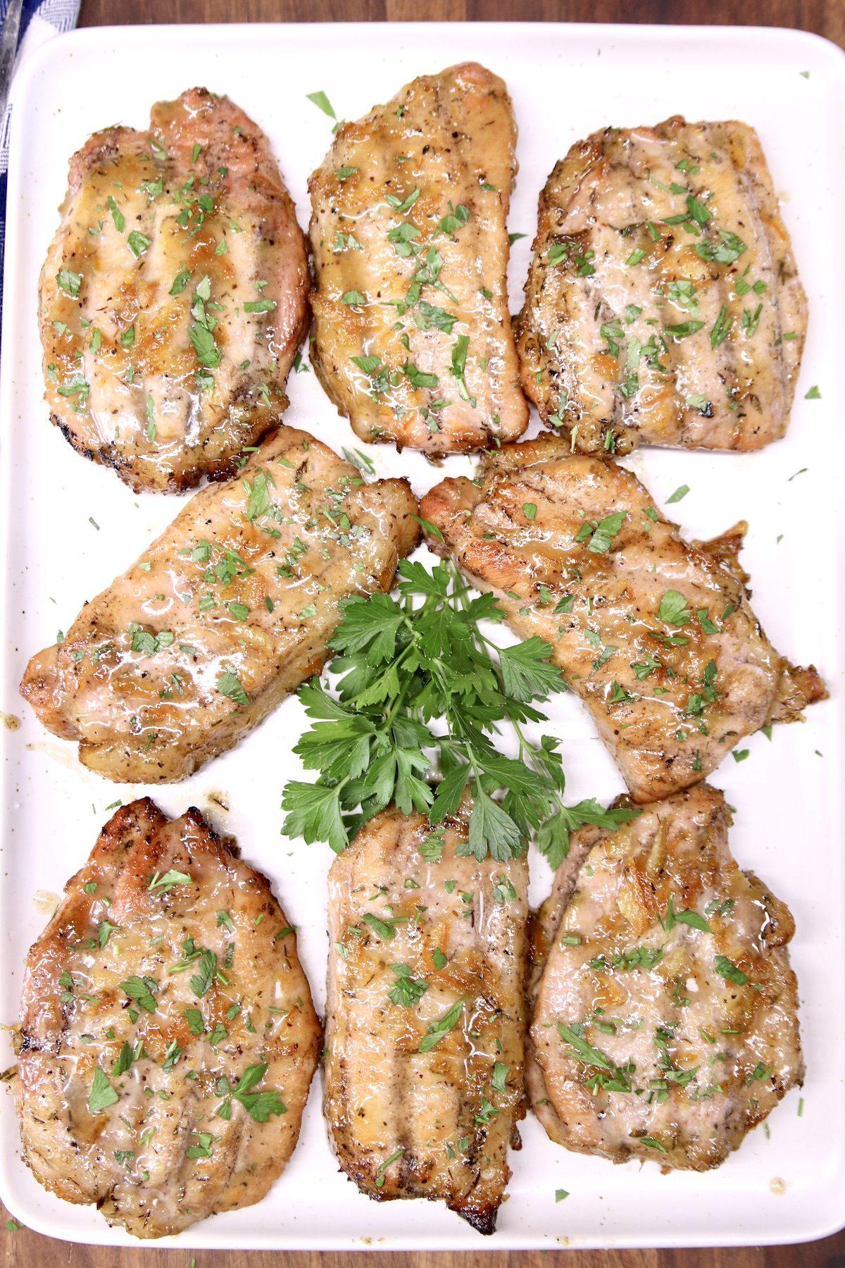 Orange Ginger Pork Chops with parsley garnish on a platter
