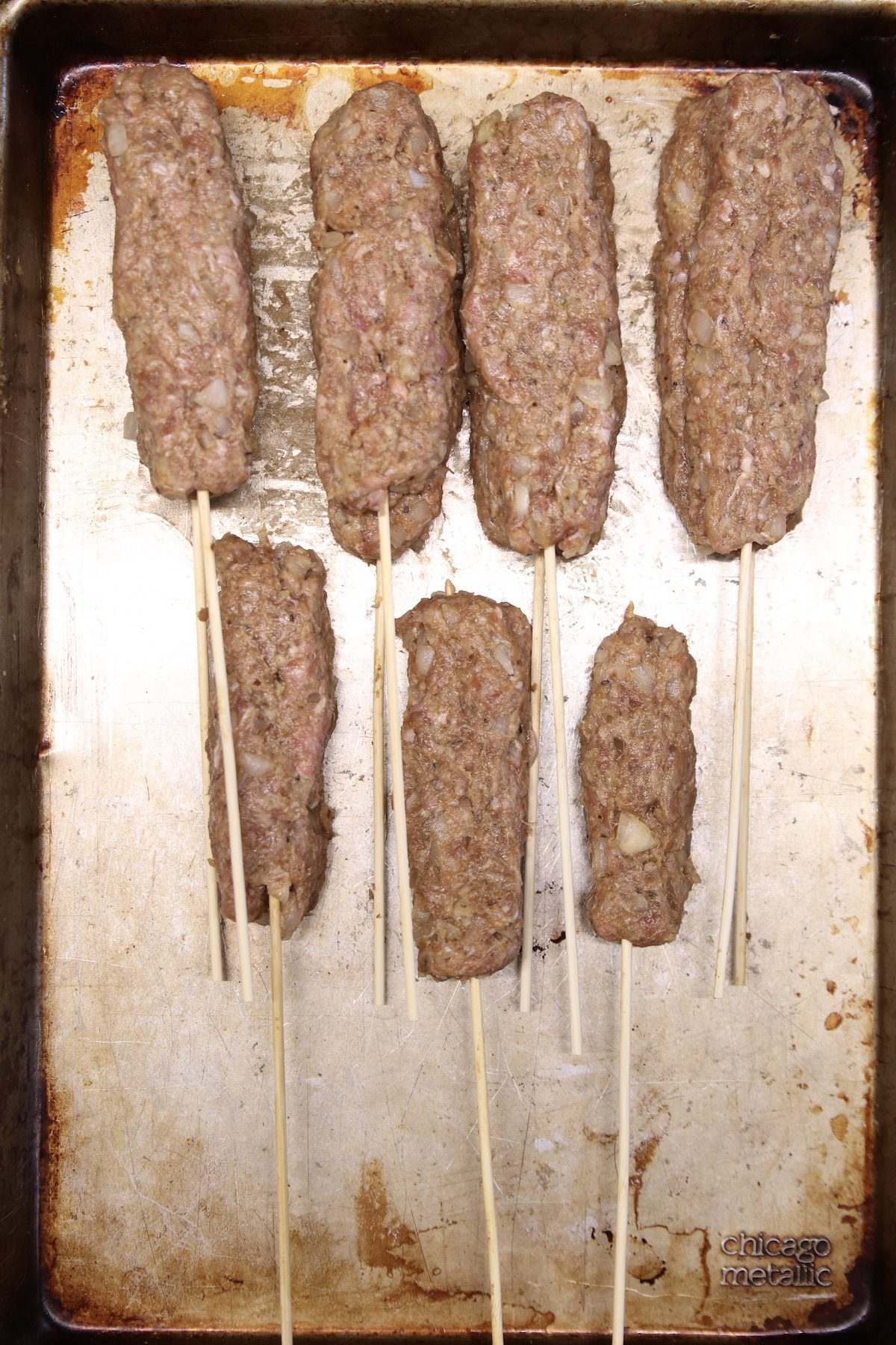 ground beef kabobs with wooden skewers ready to cook on a baking sheet