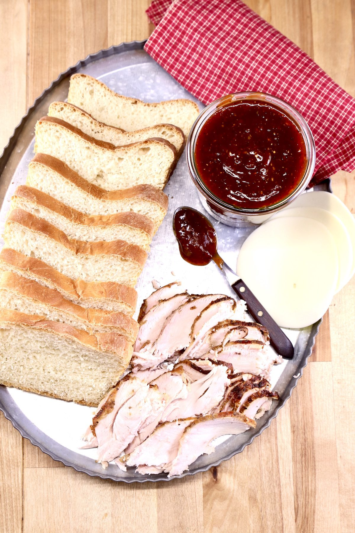 platter with sliced bread, jalapeno bbq sauce in a jar, sliced cheese and sliced smoked turkey