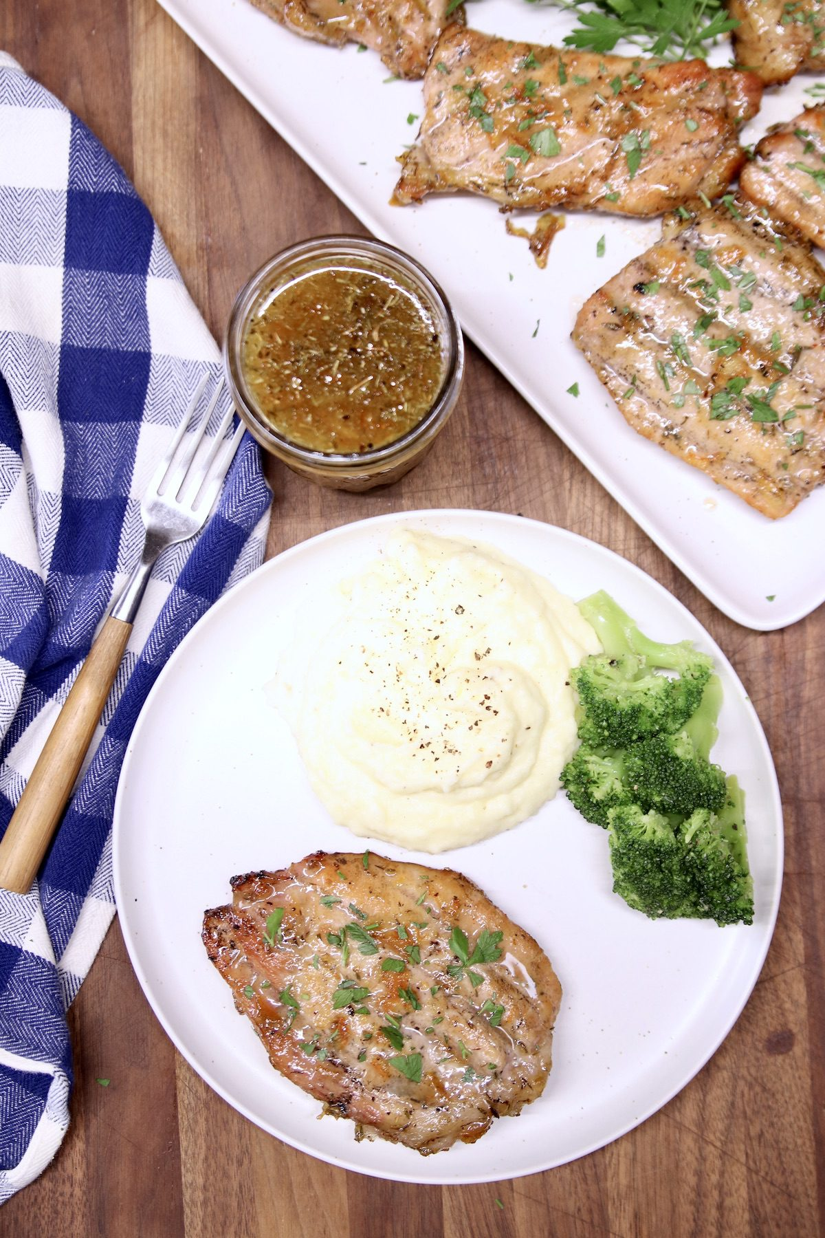 pork chop on a plate with mashed potatoes and broccoli