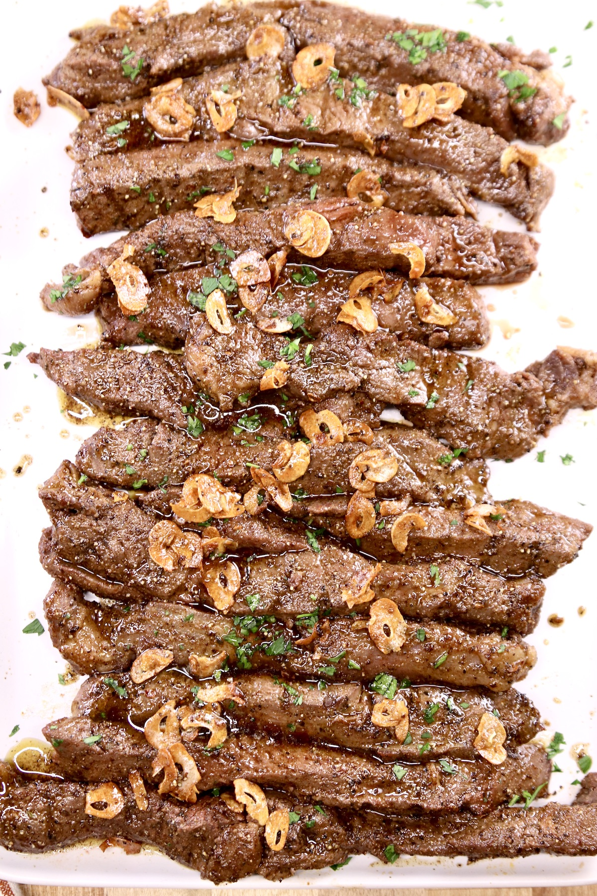 Steak Tips with garlic chips on a platter