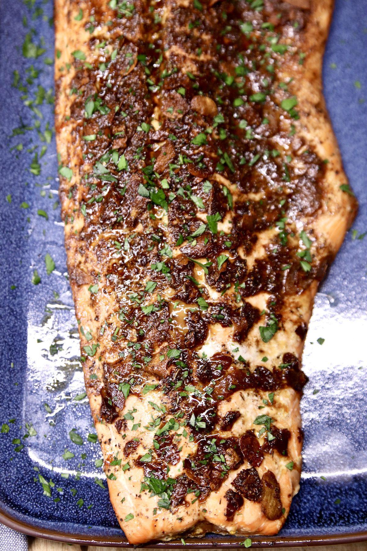 grilled garlic butter salmon fillet on a blue platter