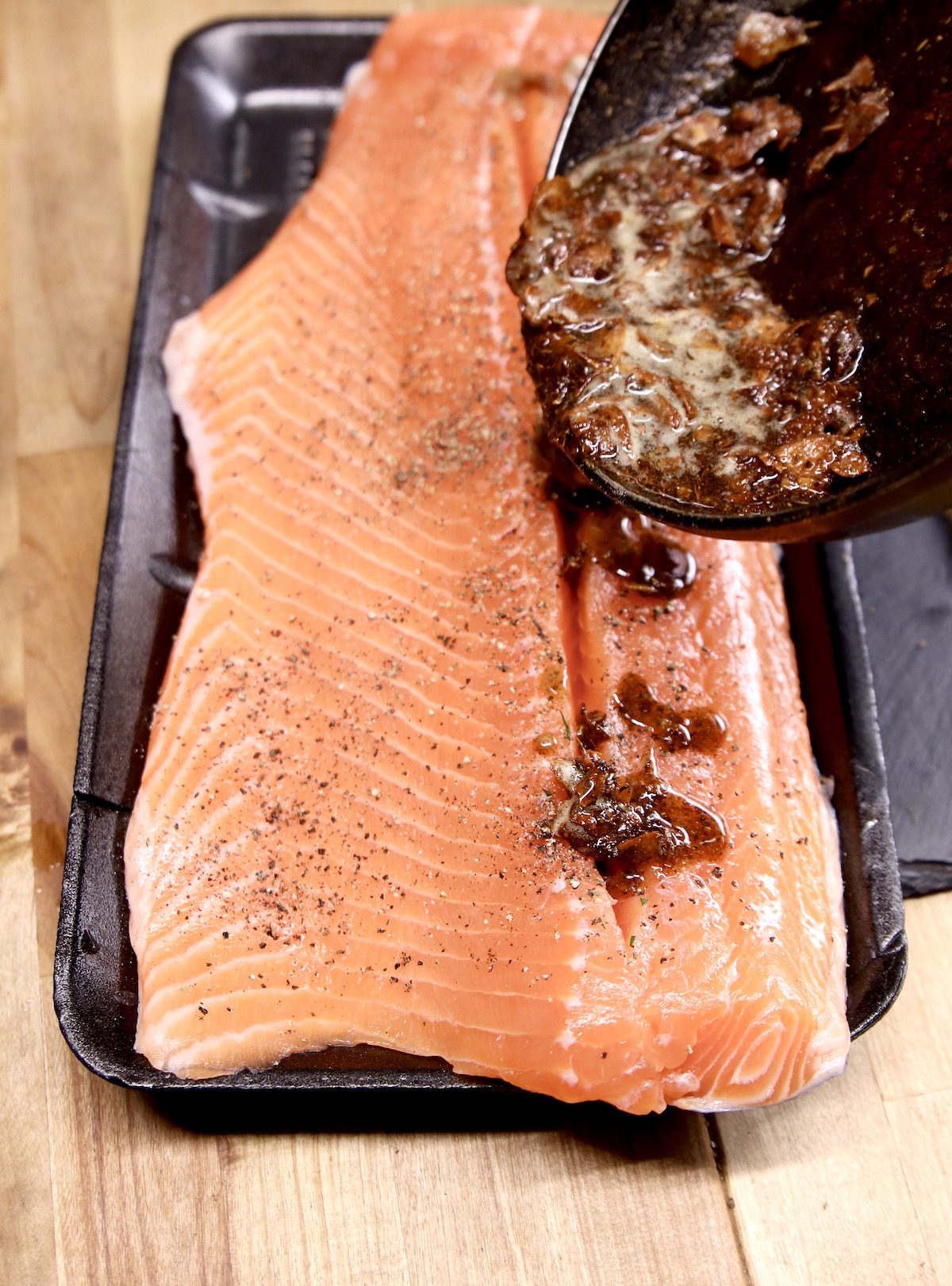 pouring garlic butter over salmon