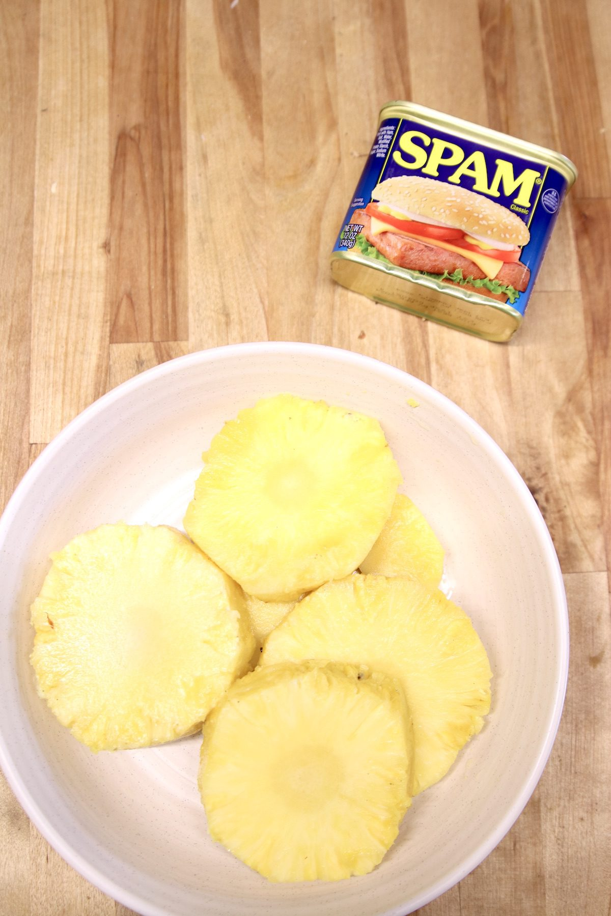can of spam with fresh pineapple cut into rounds in a bowl