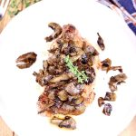 plate with pork chop topped with mushrooms