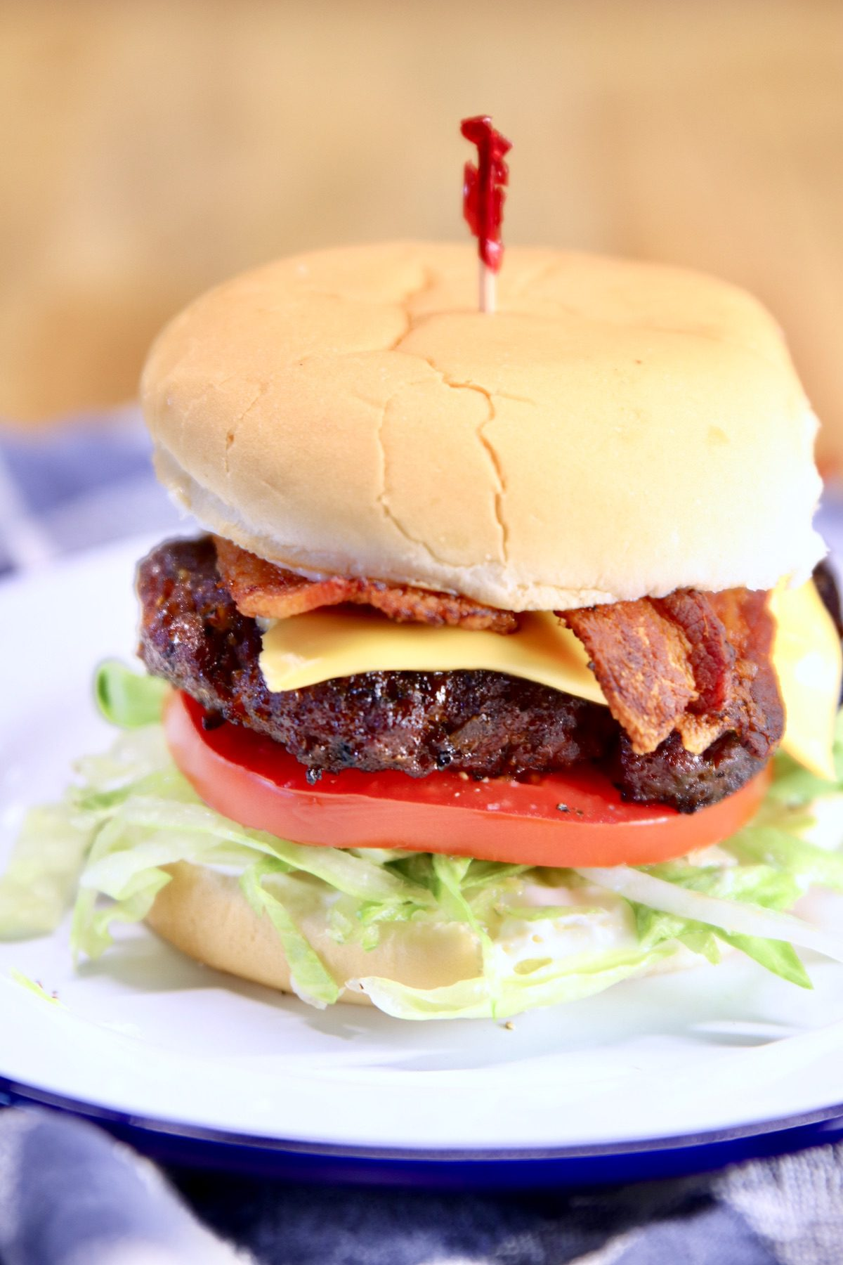 bacon cheeseburger with red top pick on a plate