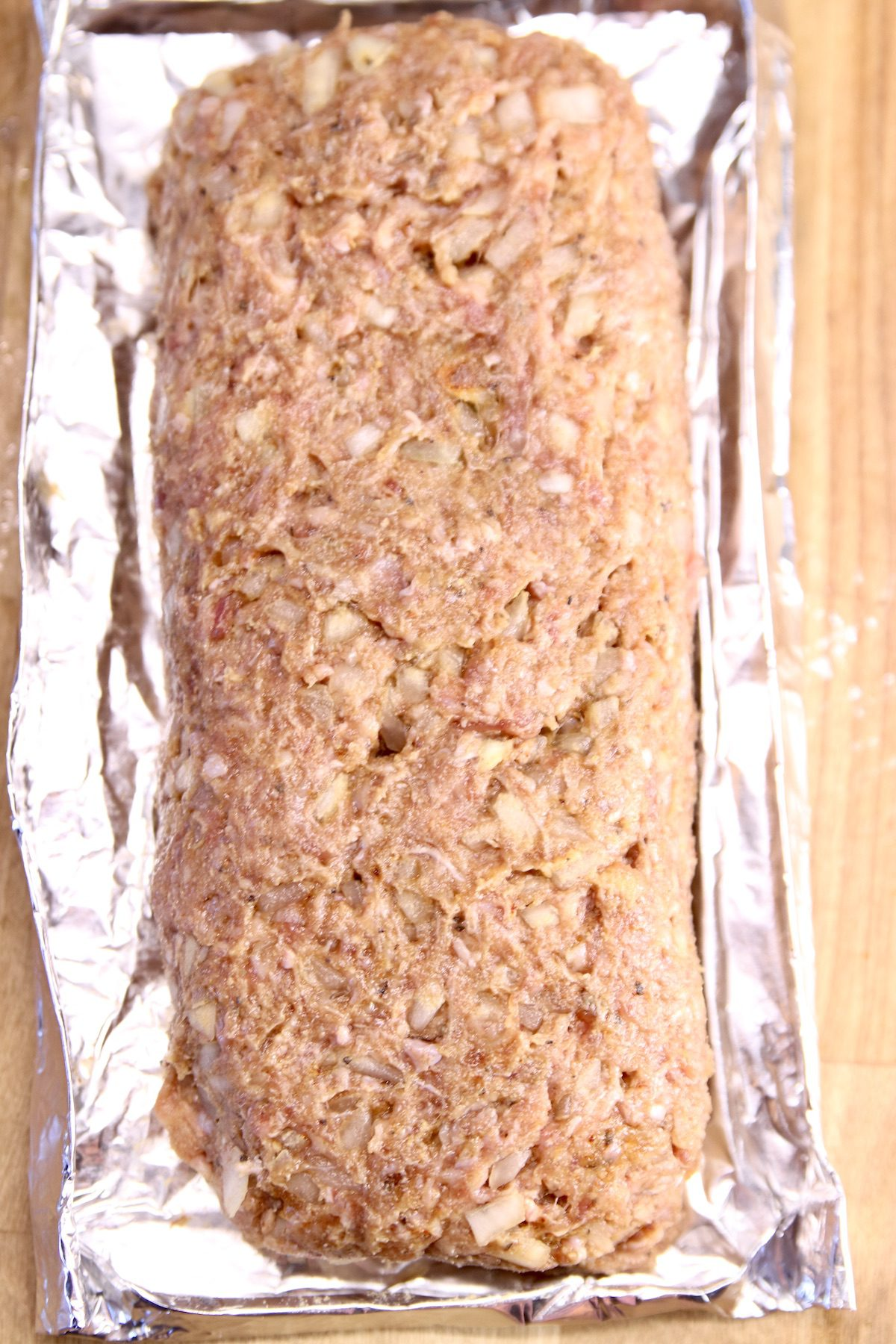 raw meatloaf mixture on a foil pan