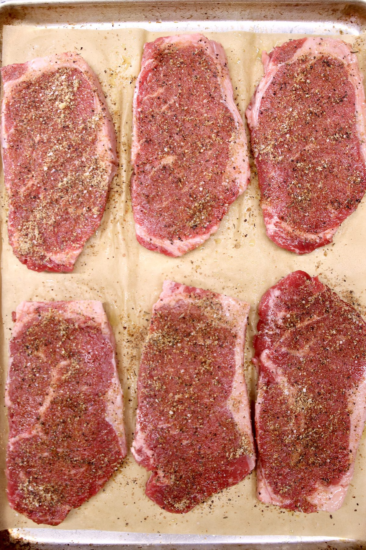 strip steaks with dry rub on a sheet pan - 6 raw steaks