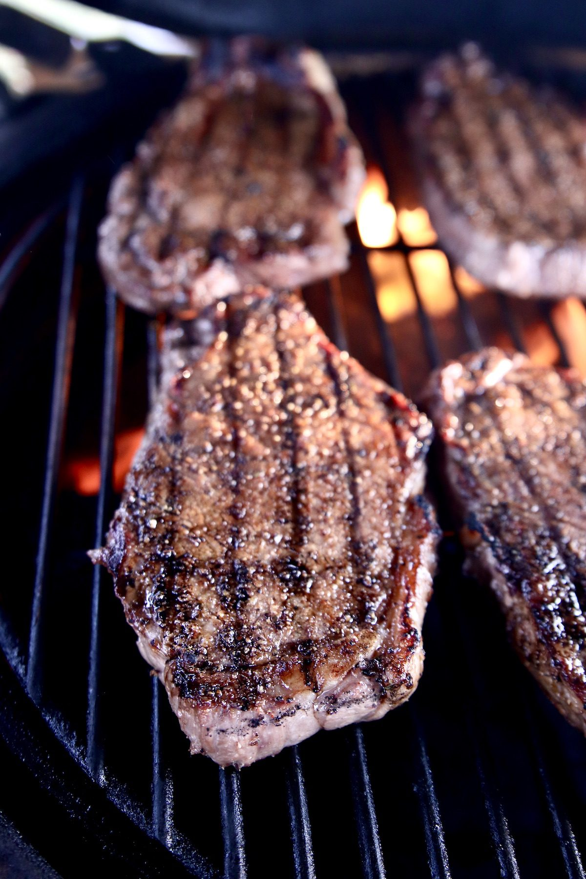 strip steaks on a grill with grill marks