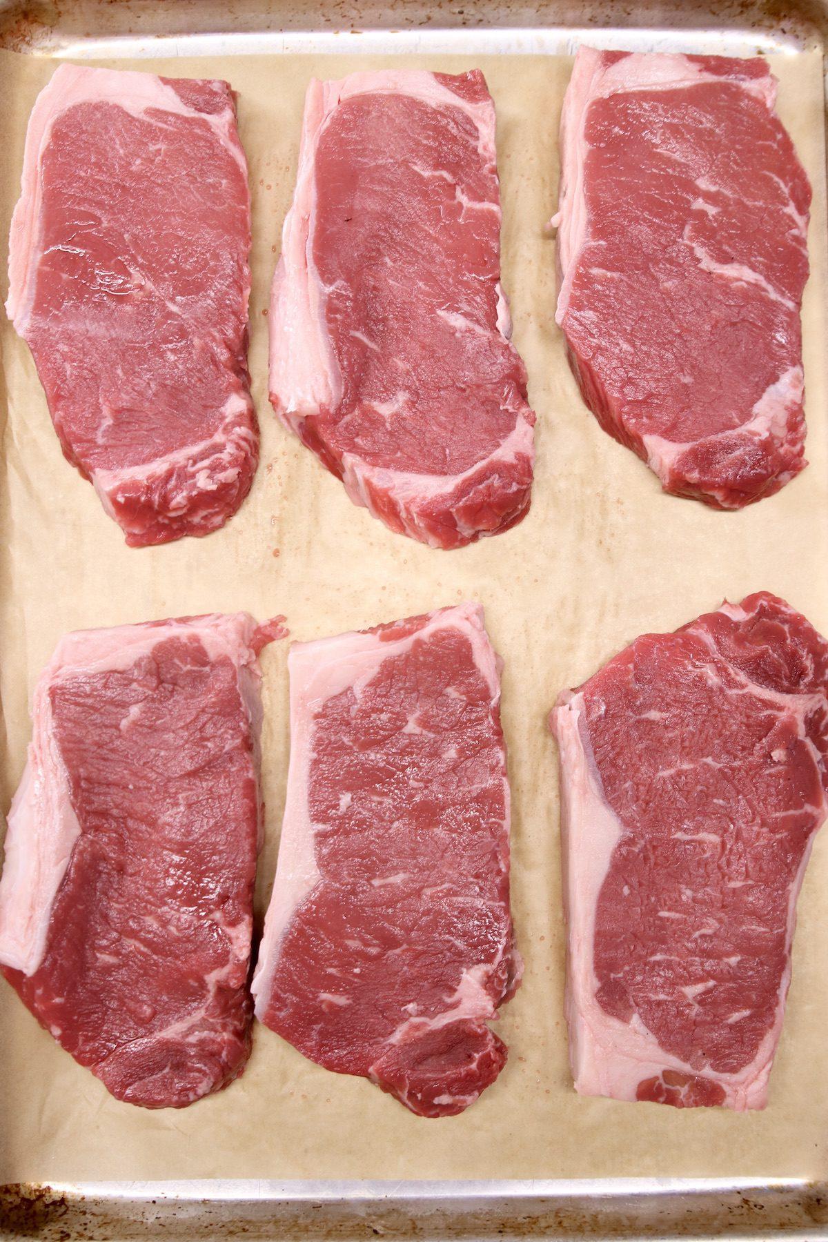 6 strip steaks on a sheet pan - raw