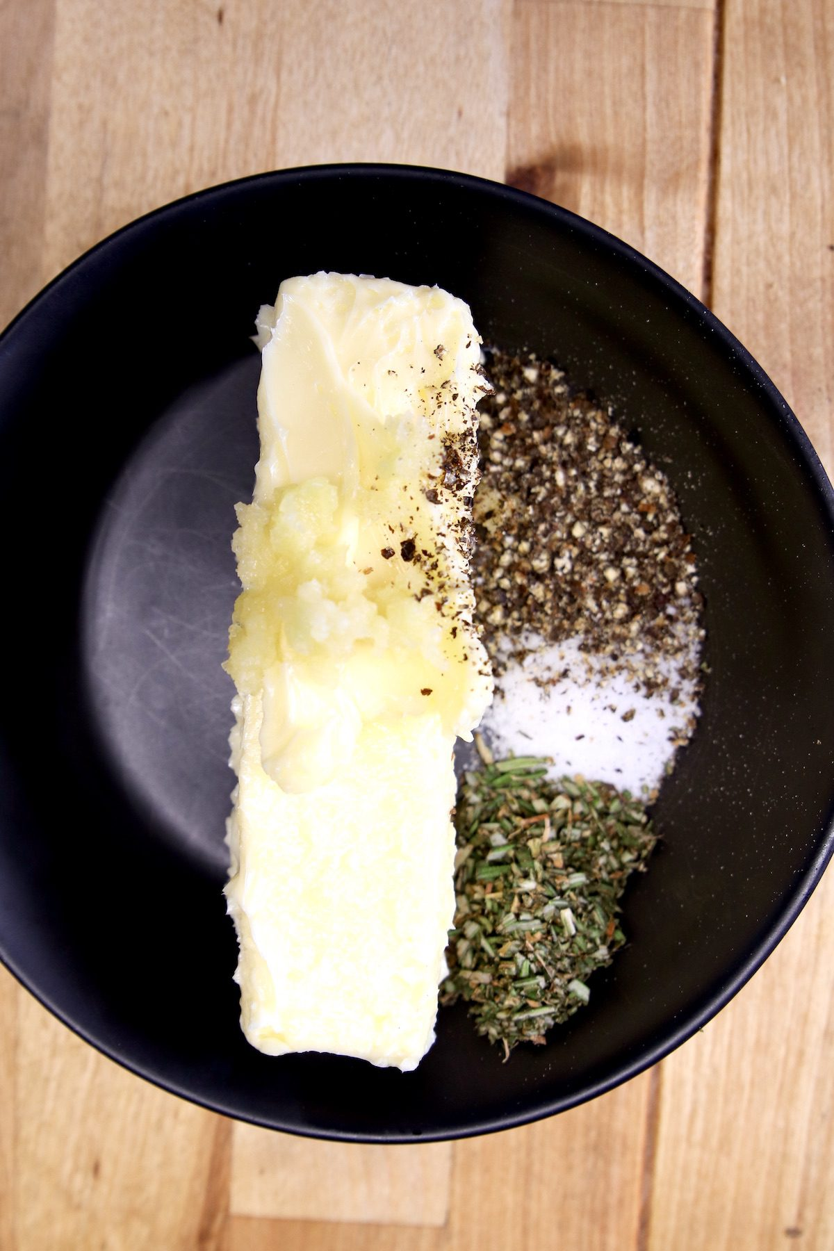 butter with minced garlic, rosemary, salt and pepper in a black bowl