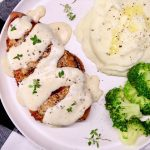 sour cream pork chop on a plate with potatoes & broccoli - text overlay