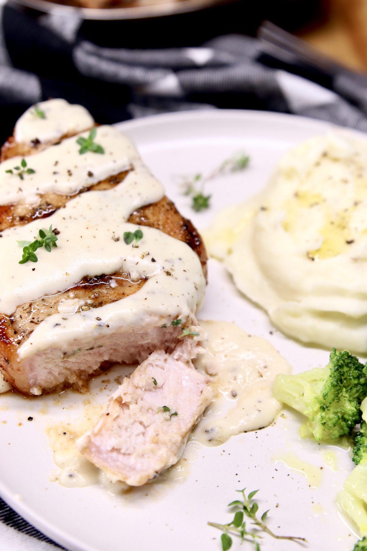 smothered pork chop on a plate, one slice - mashed potatoes & broccoli on a plate