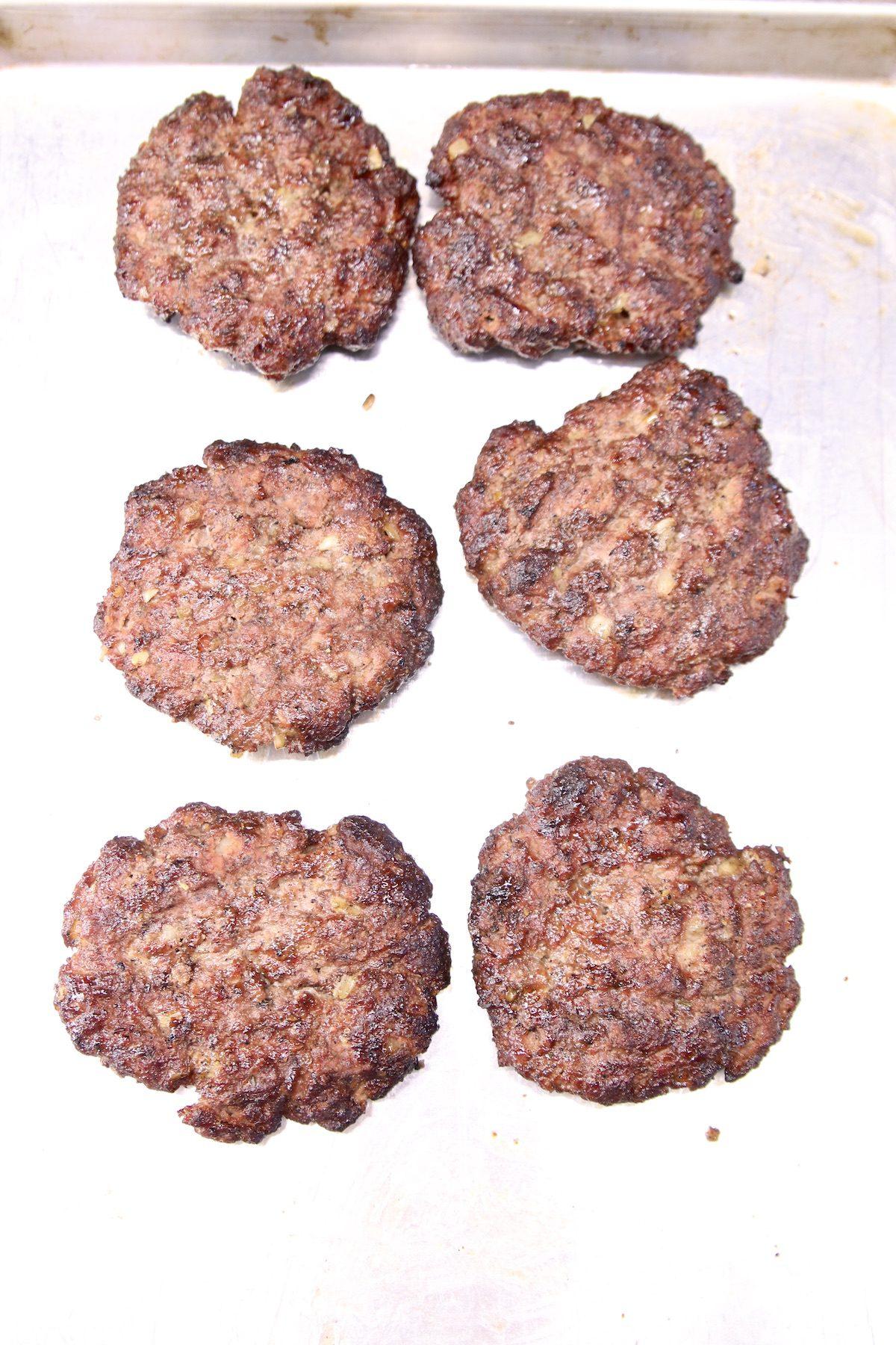 6 grilled burger patties on a sheet pan