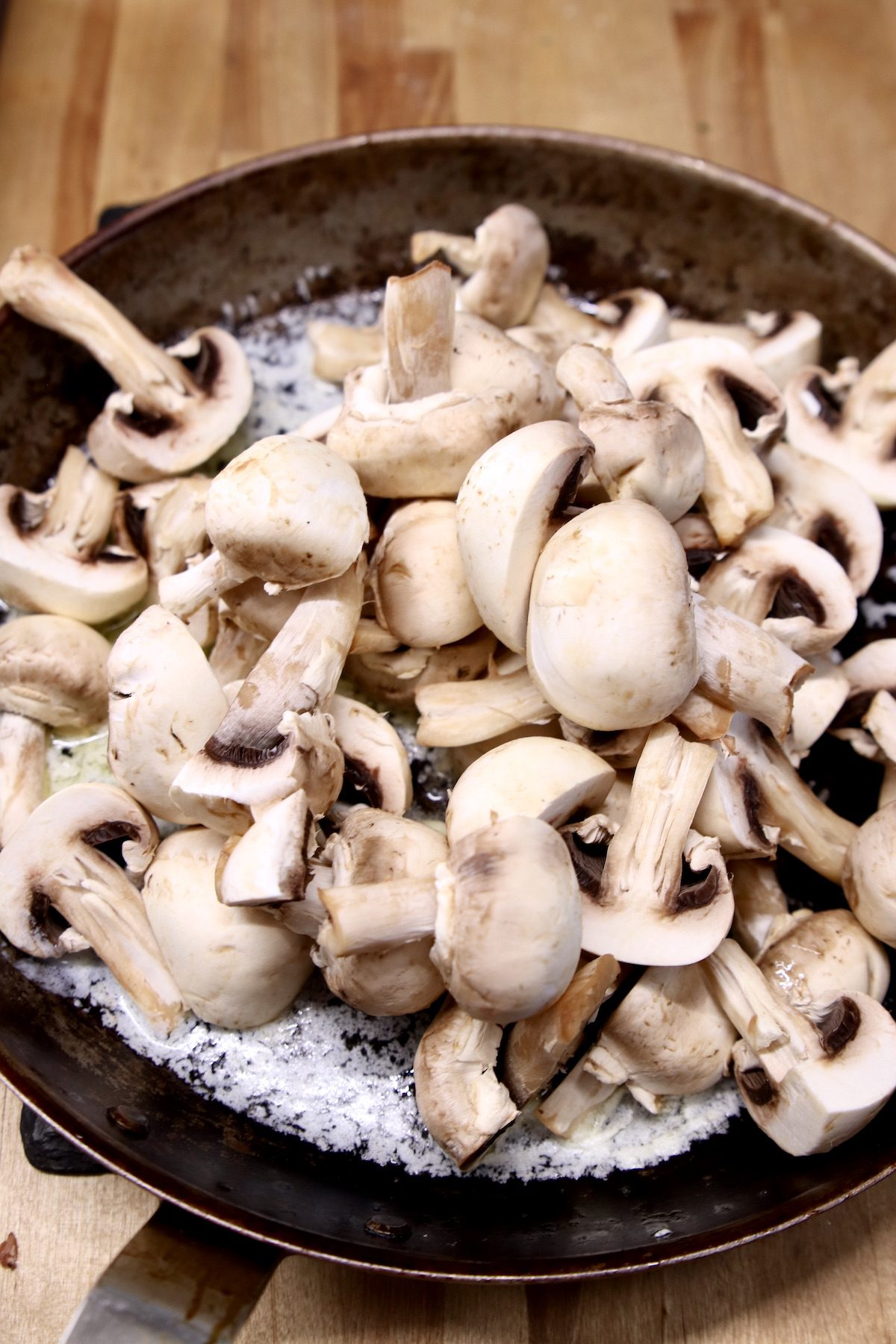 sliced mushrooms in a skillet with butter